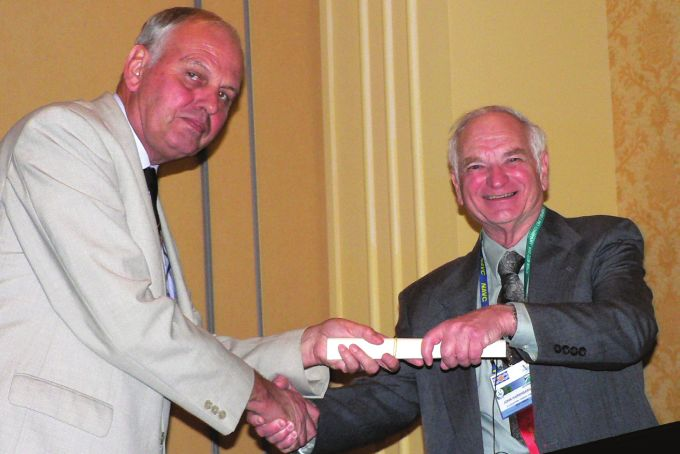Fig. 4.  Professor John Cooper presents the Elkan Lecturer, Dr John C Harshbarger, with his commemorative certifcate.